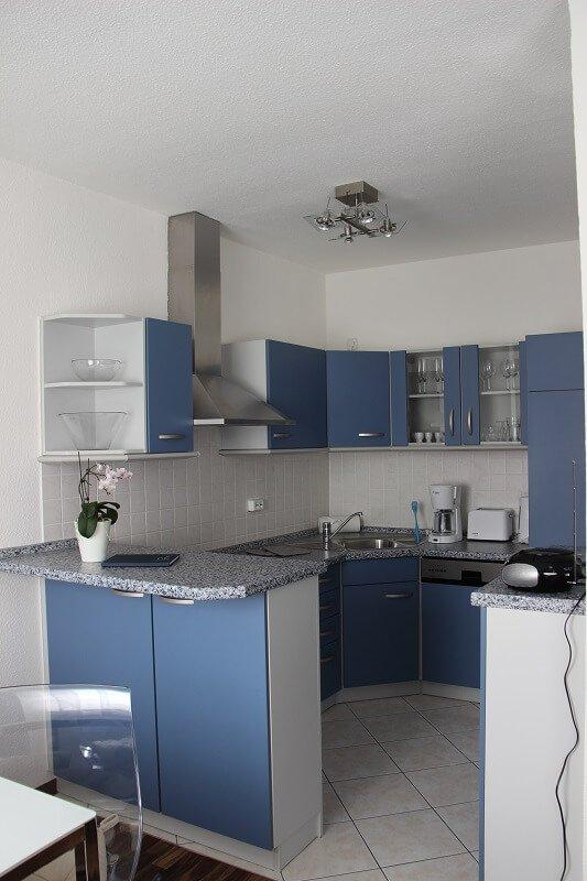 Eine blau eingerichtete Küche.