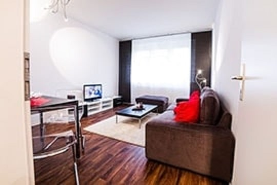 Wohnzimmer eingerichtet in rot und grau.